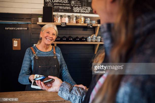 contactless payment - senior women stock pictures, royalty-free photos & images