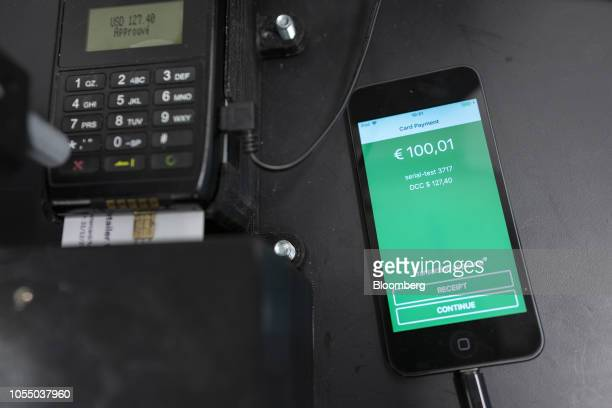 A contactless payment processing device manufactured by VeriFone Systems Inc sits beside an Apple Inc iPhone in the robotic testing room inside the...