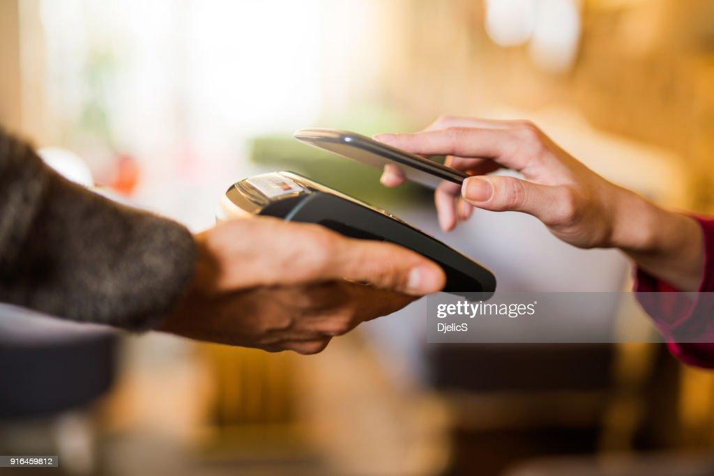 Kontaktloses Bezahlen mit einem Hand-Smartphone hautnah. : Stock-Foto
