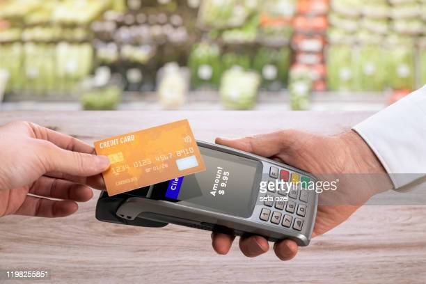 contactless payment with credit card at the grocer - contactless payment stock pictures, royalty-free photos & images