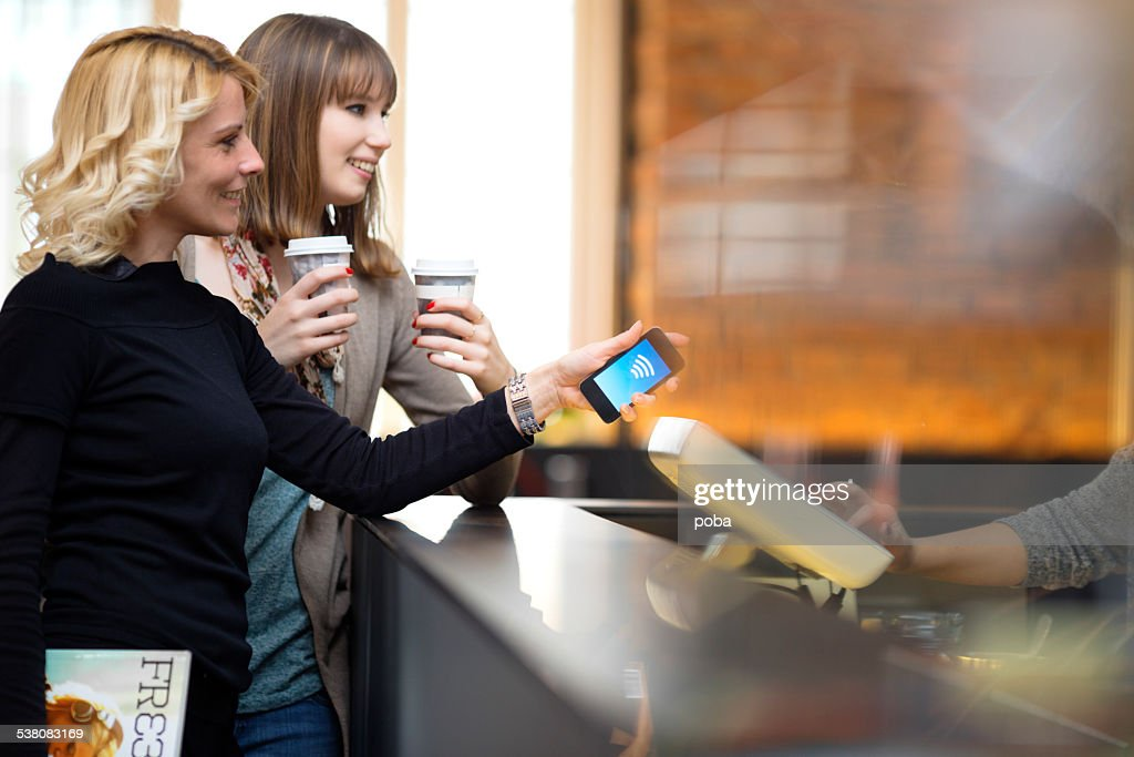 Contactless payment mit Handy im coffee bar : Stock-Foto