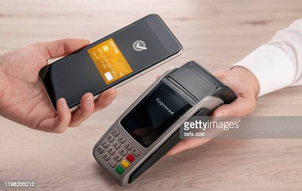 contactless payment with smart phone at the point of sale - wages stock pictures, royalty-free photos & images