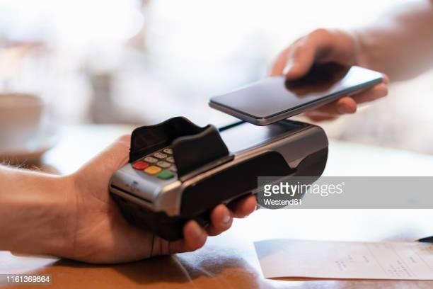 contactless payment with smartphone, close-up - zahlen stock-fotos und bilder