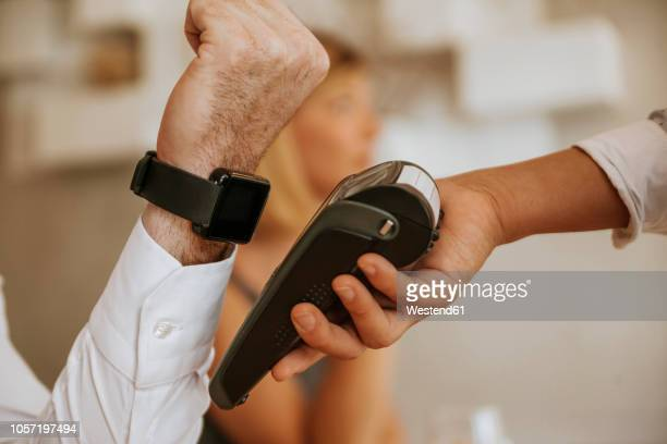 contactless payment with smartwatch in cafe - contactless payment stock pictures, royalty-free photos & images