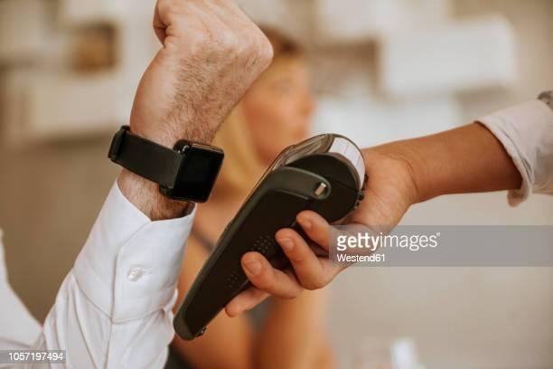 contactless payment with smartwatch in cafe - kleine uhr stock-fotos und bilder