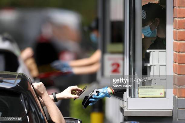 Contactless payments are made through a drive-through window as staff are seen wearing PPE equipment to minimize contact at the Burger King...