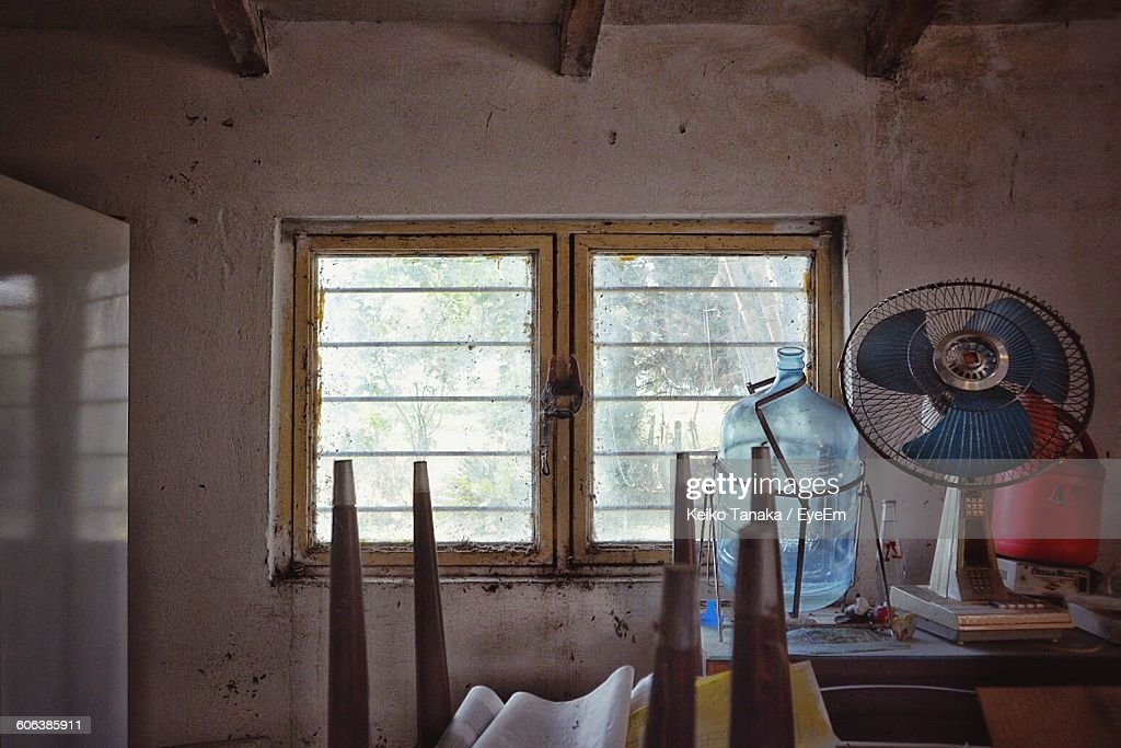 Container And Electric Fan On Table By Window In Old House : Stock Photo
