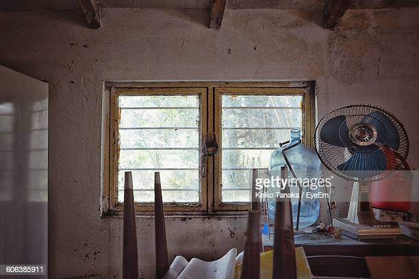 Container And Electric Fan On Table By Window In Old House