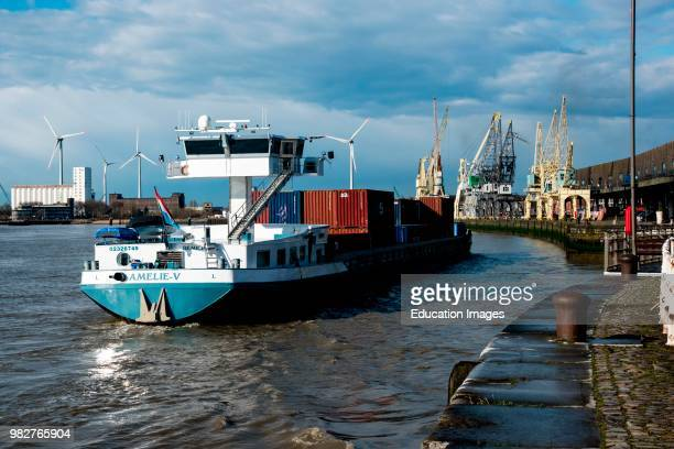 Container barge approaches dock in Antwerp, Belgium.