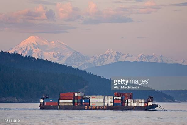 Container barge making way through Rosario Strait in the San Juan Islands, Mount Baker in the distance, Washington, USA
