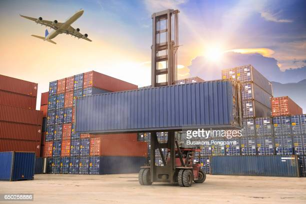 container cargo freight ship with working crane bridge at dusk for logistic import export background sunrise - container stock pictures, royalty-free photos & images