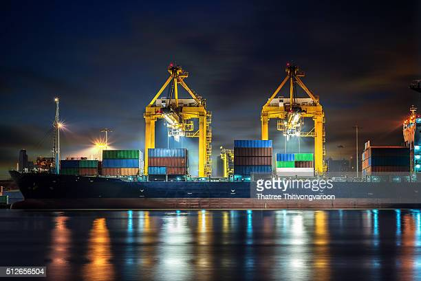Container Cargo freight ship with working crane bridge in shipyard at night for Logistic Import Export background