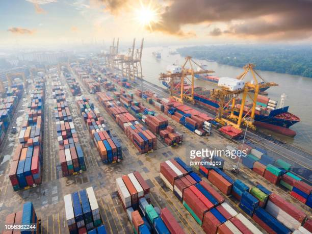 container cargo freight ship with working crane bridge in shipyard in singapore - harbour stock pictures, royalty-free photos & images