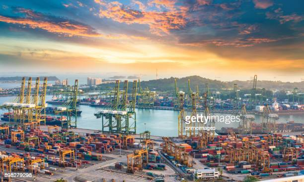 container cargo freight ship with working crane bridge in shipyard in singapore - south east asia stock pictures, royalty-free photos & images