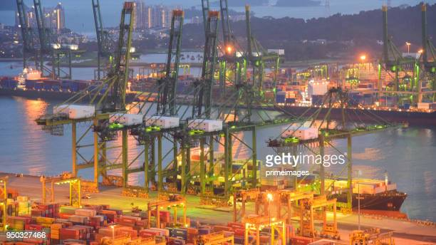 container cargo freight ship with working crane bridge in shipyard in singapore - primeimages stock pictures, royalty-free photos & images