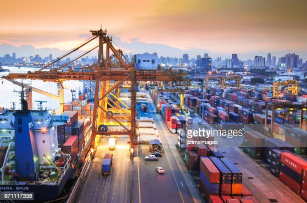 container cargo freight ship with working crane bridge in shipyard - darsena foto e immagini stock