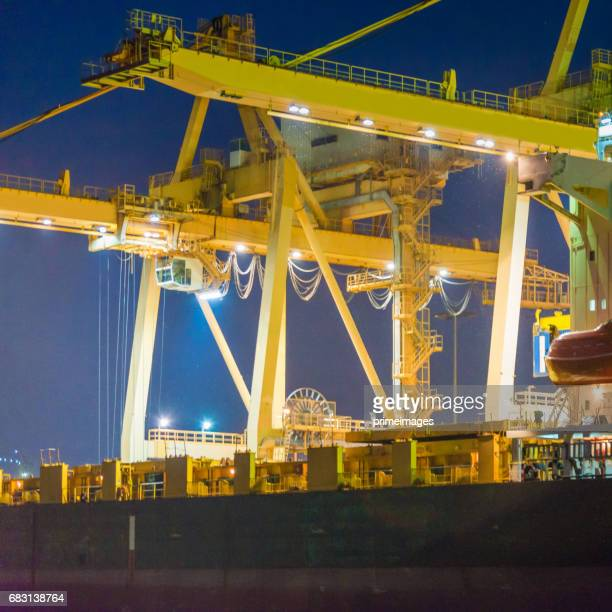 container cargo freight ship with working crane bridge in shipyard - primeimages stock pictures, royalty-free photos & images