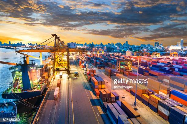 container cargo freight ship with working crane bridge in shipyard - heavy industry stock photos and pictures