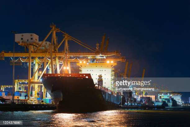 container cargo ship at terminal commercial port with working crane bridge loading container to the ship at night. transporting shipment container for business logistics, import export, shipping or transportation. - shipyard stock pictures, royalty-free photos & images