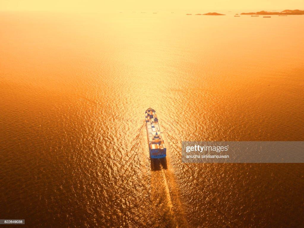 container cargo Ship is running in sea orange light . : Stock Photo