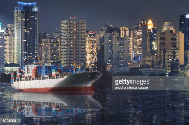 container cargo ship reflect in water with city background .