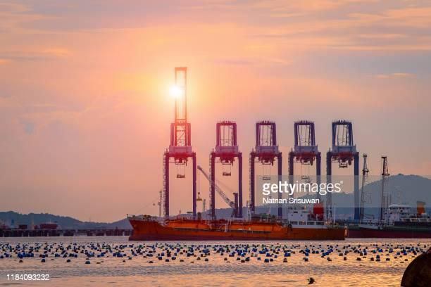 container cargo ship with working crane bridge. - handel treiben stock-fotos und bilder