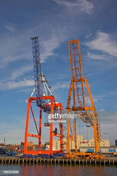 Container cranes in late afternoon against sky.