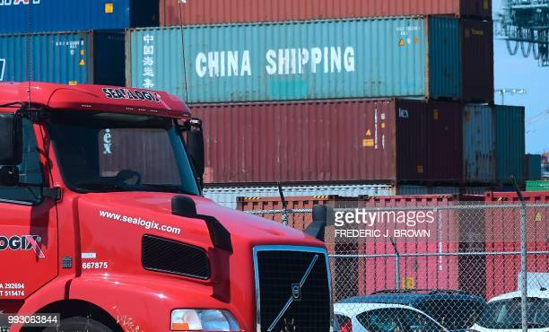 A container delivery truck drives past stacked piles of shipping containers at the Port of Long Beach in Long Beach California on July 6 including...