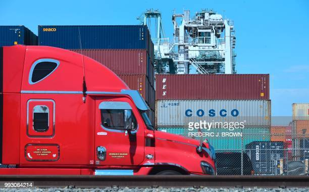 A container delivery truck passes containers stacked at the Port of Long Beach in Long Beach California on July 6 including one from COSCO the...