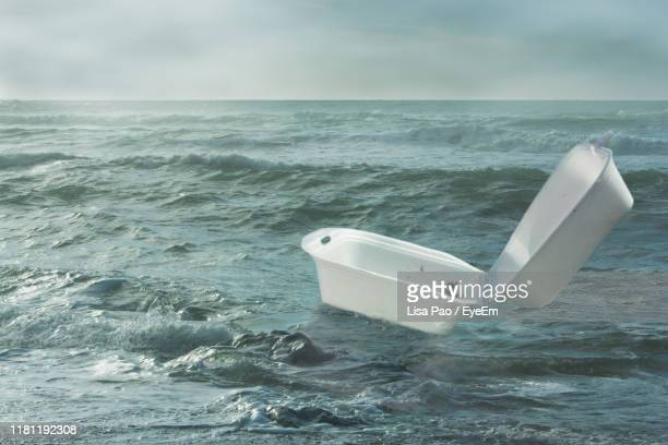 container floating in sea against sky - water pollution stock pictures, royalty-free photos & images