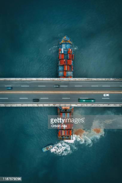 道路橋の下を航行するコンテナ貨物船 - 貨物船 ストックフォトと画像