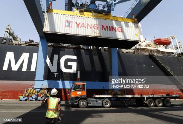 A container is loaded on a truck parked near a docked ship at the harbour of Umm Qasr south of Basra in southern Iraq after the port reopened on July...