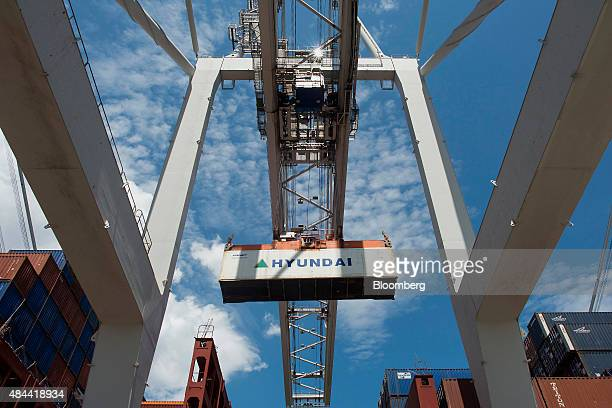 A container is loaded onto a ship at the Port of Savannah in Savannah Georgia US on Friday Aug 14 2015 The trade deficit in the US widened in June as...