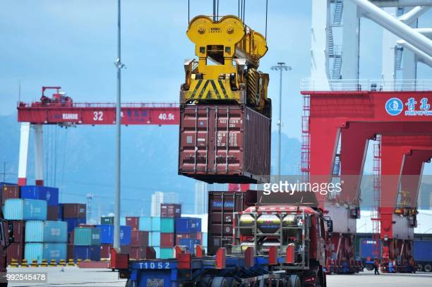 A container is transferred at a port in Qingdao in China's eastern Shandong province on July 6 2018 Punishing US tariffs on Chinese imports took...