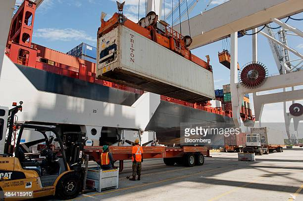 A container is unloaded from a truck onto a cargo ship at the Port of Savannah in Savannah Georgia US on Friday Aug 14 2015 The trade deficit in the...