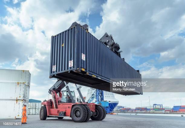 container lift with shipping container in port - commercial dock stock pictures, royalty-free photos & images