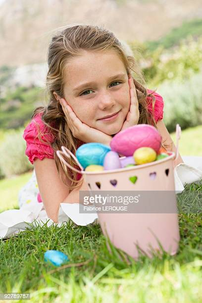 Container of Easter eggs in front of a girl
