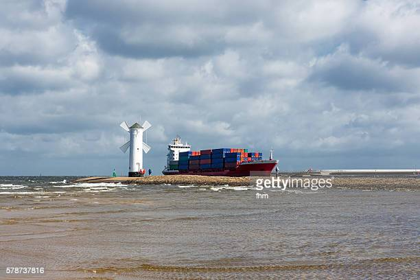 Container ship arrives at Swinemünde/ Stawa Młyny - a beacon (German: Mühlenbake) in the shape of a windmill/ Poland