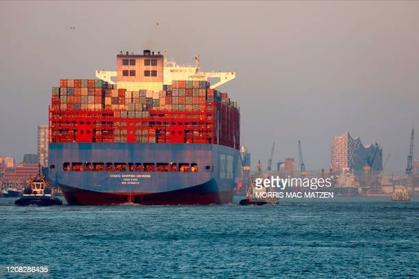 A container ship arrives at the harbor of the northern German city of Hamburg on March 26 2020 German consumer confidence has hit its lowest level...