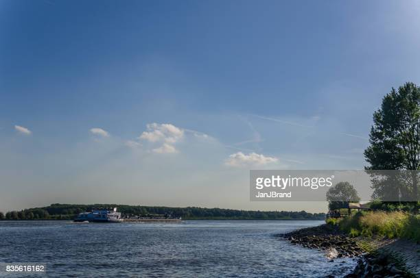 container ship at old meuse - meuse river stock photos and pictures