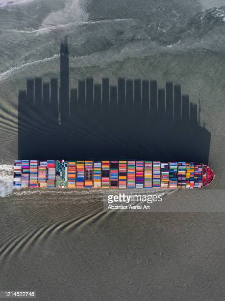container ship casting a shadow shaped like a city skyline, netherlands - nautical vessel stock pictures, royalty-free photos & images