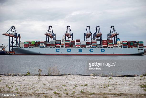 Container ship Cosco England operated by the China Ocean Shipping Group Co sits docked as shiptoshore cranes stand at the Euromax Terminal in the...
