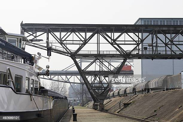container ship, cranes and freight train in port - basel port stock photos and pictures