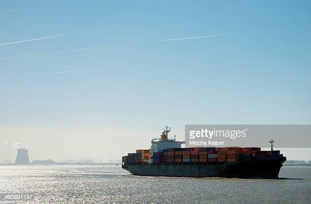 container ship leaving antwerp harbor, belgium - antwerpen provincie stockfoto's en -beelden