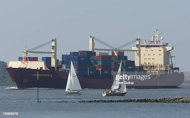 A container ship passes sailboats on the Elbe River on its way to Hamburg August 4 2007 at Wedel Germany Northern Germany with its busy ports of...
