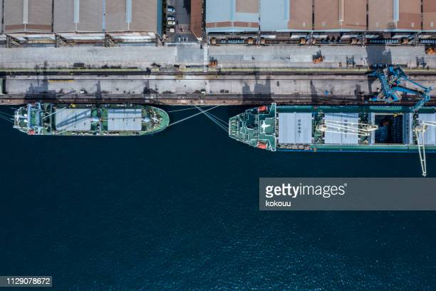 a container ship was anchored at a port with a logistics warehouse. - moored stock pictures, royalty-free photos & images