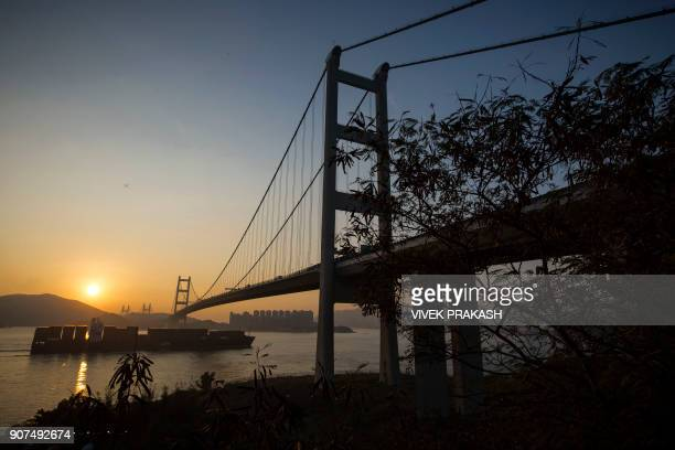 TOPSHOT A container shipping vessel passes beneath the Tsing Ma bridge during sunset in Hong Kong on January 20 2018 / AFP PHOTO / VIVEK PRAKASH