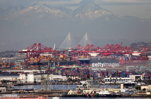 Container ships and shipping containers are viewed at the Port of Los Angeles with the Port of Long Beach in the distance on February 1, 2021 in San...