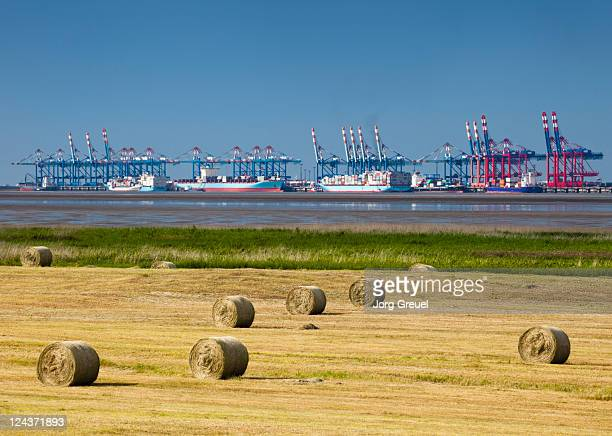 Container terminal and hay bales on a field