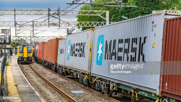 container train passes london midland commuter service in railway station - maersk stock pictures, royalty-free photos & images